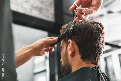 Hairdresser undergoing hairdo at salon