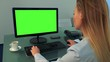 A woman works on a computer with a green screen in an office