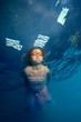 Beautiful little girl swims underwater in a beautiful gown and looks up. Portrait. Shooting under the water surface. Vertical orientation