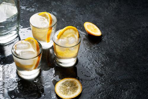Photo  Bottle of vodka with shot glasses and lemon.