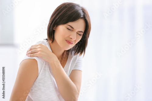 Canvas Print Beautiful young woman suffering from pain in shoulder at home