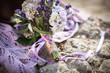Golden wedding rings are on bouquet from lavender, hydrangea, pi