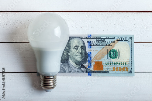 Photographie  led bulb with money on table.