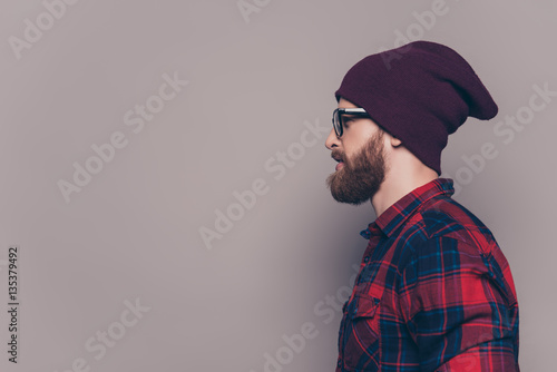 Valokuva  Side view of handsome bearded hipster man in violet cap and glas