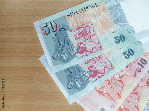 Photo  Singapore Dollar bank notes (10 and 50 Dollars) on wooden table background, top