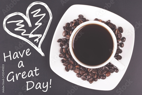 Photo  Cup of coffee with have a great day message. Table top view