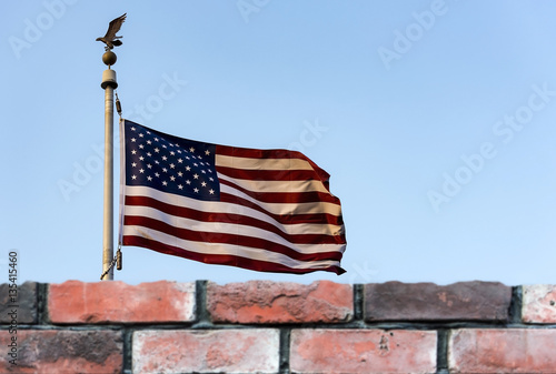 Photo  American flag and defocused brick fence, the United States confrontation and ref