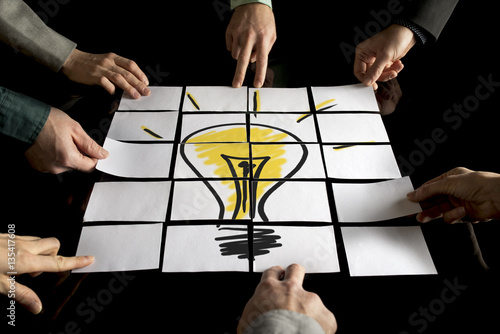A team of seven businesspeople forming a yellow light bulb