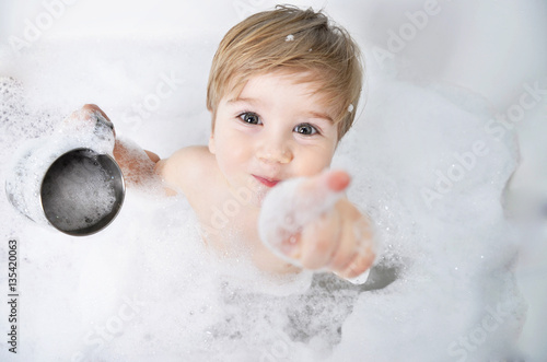 Photographie small child takes a bath with foam