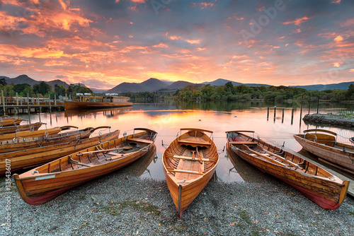 Fototapeta A fiery sunset over boats on the shore of Derwentwater at Keswick in the Lake Di