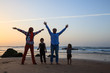 Happy family of four have fun on winter beach in Algarve, Portugal. Mother, father and two kids boy traveling