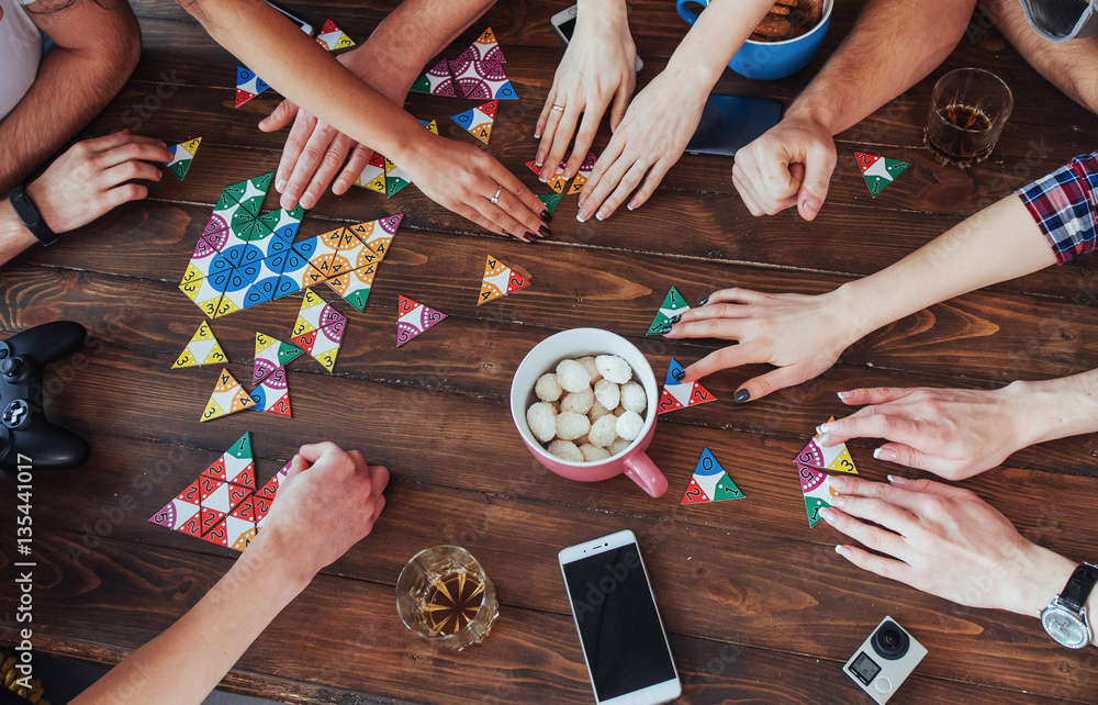 Fototapeta Top view creative photo of friends sitting at wooden table.  having fun while playing board game