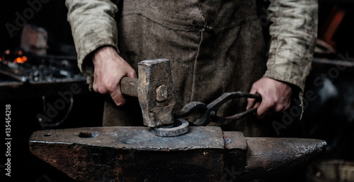 Photo blacksmith forges item on the anvil