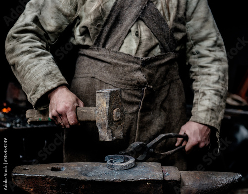 Wallpaper Mural Rustic blacksmith forges item on the anvil