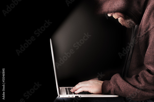 Photo  Male computer hacker wearing a hooded top leaning over a laptop in the dark