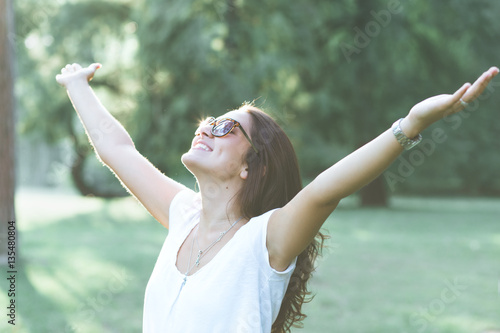 Beautiful brunette woman expressing freedom outdoors with her arms outstretched.