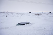 Car Buried To Its Roof In Deep Snow Not Far From The Road. North Dakota, USA