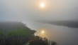 Brilliant & bright mid-summer sunrise on narrow passage of a lake. Warm water & cooler air at daybreak create local misty fog. Quiet water along marshy lakeside.