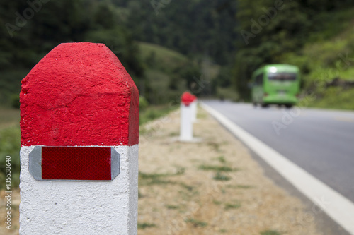 Red and white painted milestones in range on a country road under the sunlight Plakat