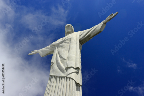 In de dag Rio de Janeiro Redeemer Christ of Rio de Janeiro in the top off Corcovado Hill. Bottom view of the statue, the blue sky and clouds at the background.