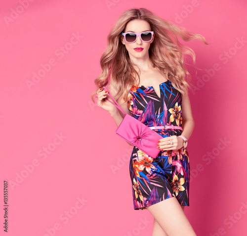 Fashion woman in Trendy Spring Summer Dress. Stylish wavy hairstyle, fashion Sunglasses, Summer Floral Outfit. Glamour Blond lady in Sexy Jumpsuit, fashion pose. Playful Girl,Luxury summer Pink Clutch Wall mural