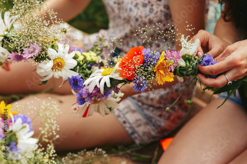 фотография  Young hipster women making flower wreaths circle closeup