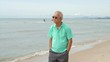 Asian senior man wearing sunglasses and thinking about life planning next to the sea