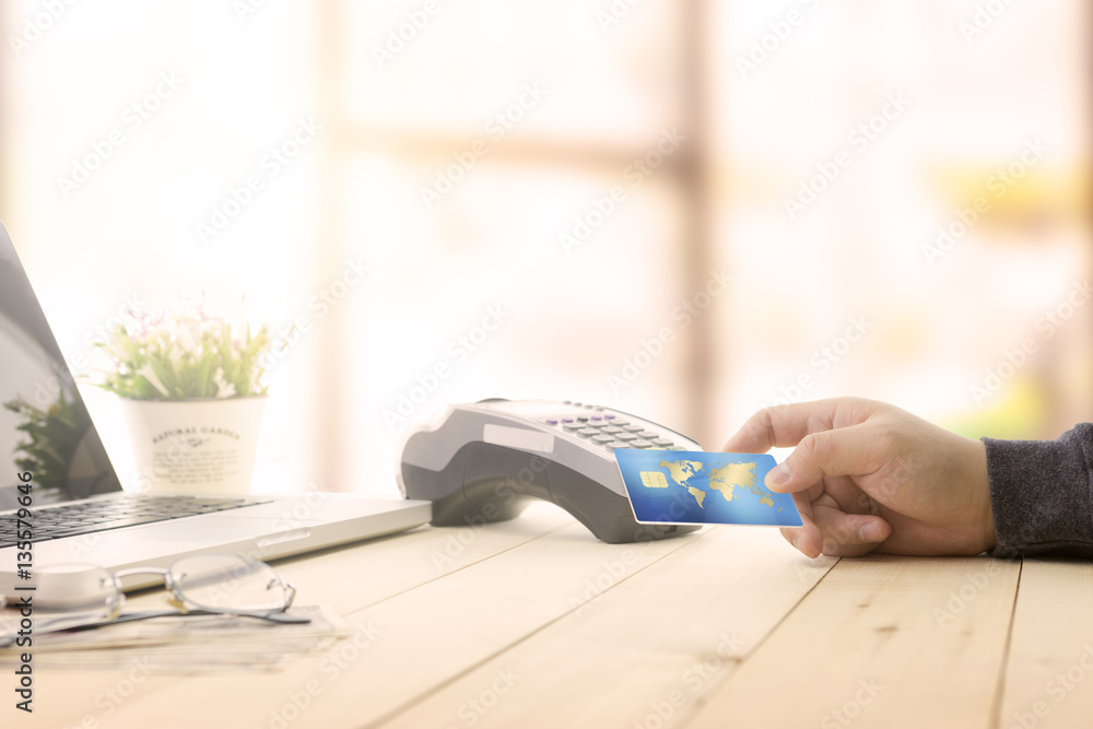 Fototapeta Cashier or Adult hand holding a Credit card over EDC machine or credit card terminal intent to order goods/ booking from home office. IOT online market shopping advertising. This is fake credit card.