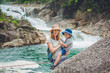 Mother and son relaxing under a waterfall. Vacation concept