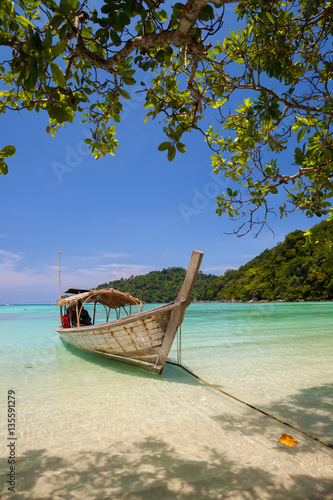 Wall Murals Bali Long tail boat on tropical white beach with moutain backgroud , located at south island, Satun province, Thailand