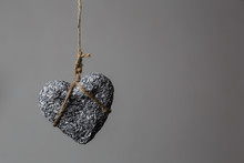 Stone Heart In Jute Bondage Hangs Against Grey Background With Copy Space, Valentine's Day Concept,
