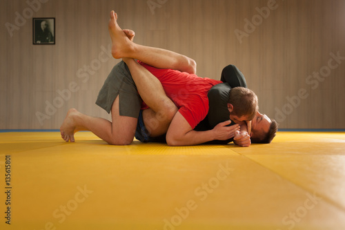Photo  MMA fighter holding his opponent with triangle hold and trying to choke his neck