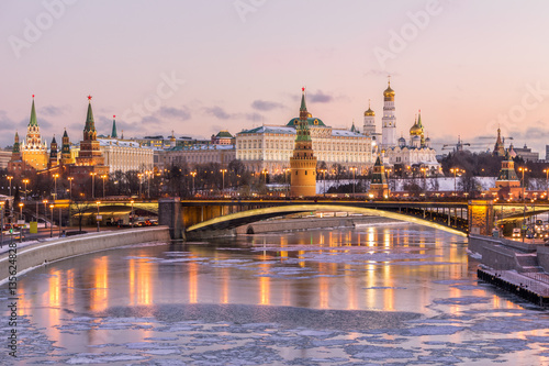 Illuminated Moscow Kremlin and Moscow river in winter morning. Pinkish and golden sky with clouds. Russia