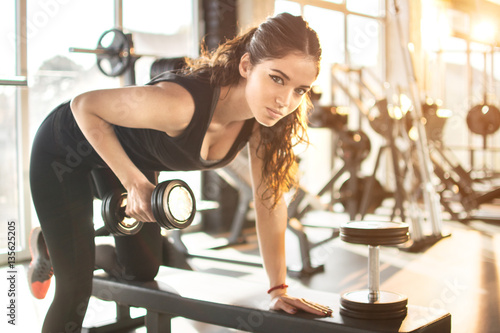 Fotografie, Obraz  Young woman working out in gym and lifting weights.