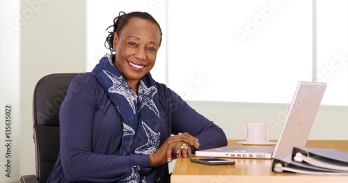 Valokuva A black businesswoman poses for a portrait at her desk