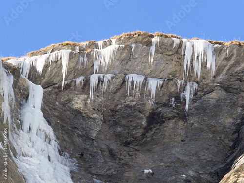 Fotografia, Obraz  Ice stalactites and frozen waterfall on a rock face