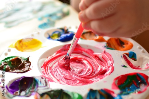 Fotografie, Obraz  Child mixing paint on a palette of colorful paint