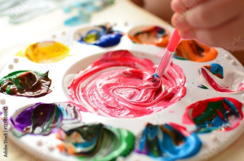 Fotografie, Obraz  Child mixing paint on a palette of colorful paint