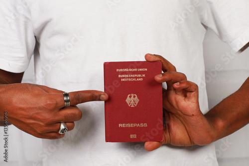 Valokuva  schwarze Hand zeigt auf deutschen Pass