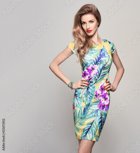 Fashion woman in Trendy Spring Summer Dress. Stylish wavy hairstyle, fashion Makeup, Summer Floral Outfit. Glamour Blond lady in Sexy Bodycon, fashion pose. Playful Girl, Luxury summer Accessories Wall mural