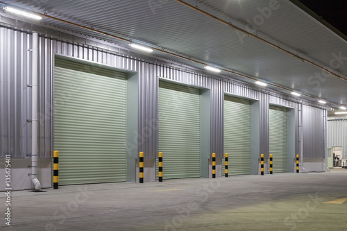 Deurstickers Industrial geb. Shutter door or roller door and concrete floor outside factory building use for industrial background.