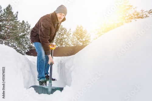 Fototapeta Man in winter clothes cleans snow shovel on courtyard at sunny day obraz