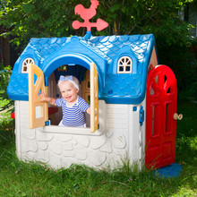 Little Baby Girl Wearing White-blue Striped Summer Dress Looking Out From Plastic Play House Window In A Playground