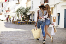 Two Female Friends On Vacation Shopping In Ibiza, Back View