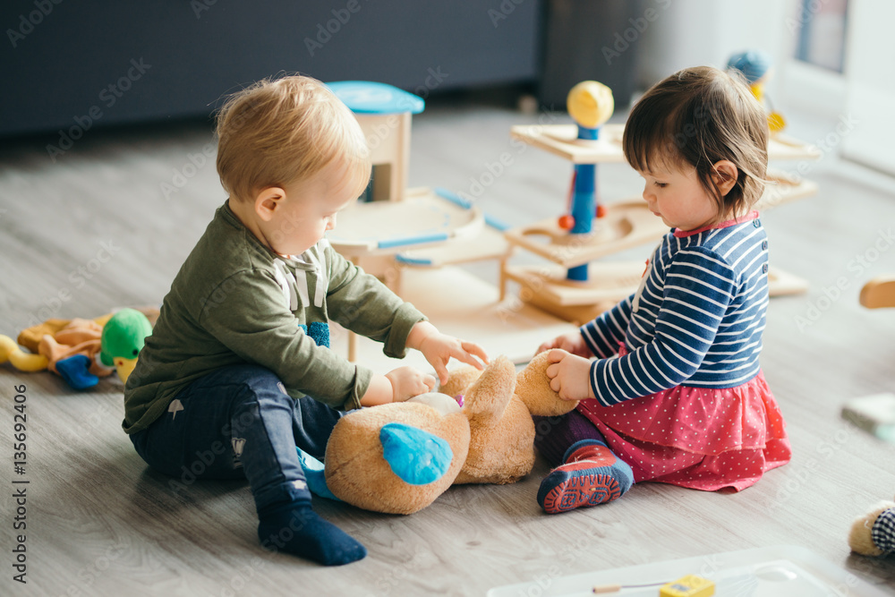 Fototapety, obrazy: little girl and boy playing with toys by the home