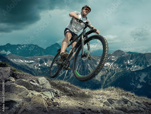 Man in helmet and glasses stay on the bicycle under sky with clo #135698045