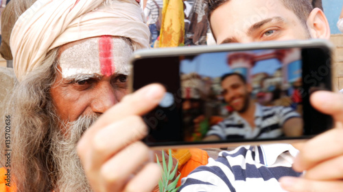 Photo  Tourist taking a selfie with Sadhu Holy Man in India