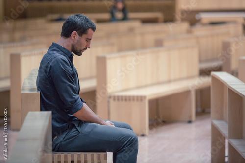 Young beard man wearing blue shirt praying in modern church Fototapeta