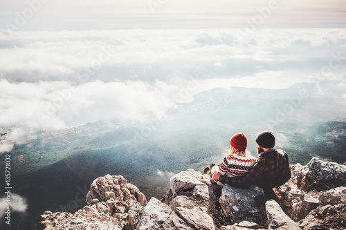 Poster  Couple travelers Man and Woman sitting on cliff relaxing mountains and clouds aerial view  Love and Travel happy emotions Lifestyle concept