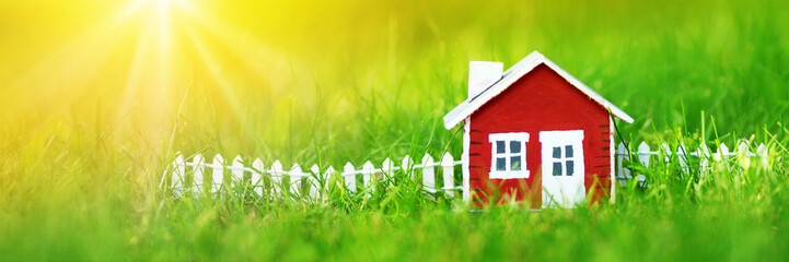 red wooden house model on the grass in garden